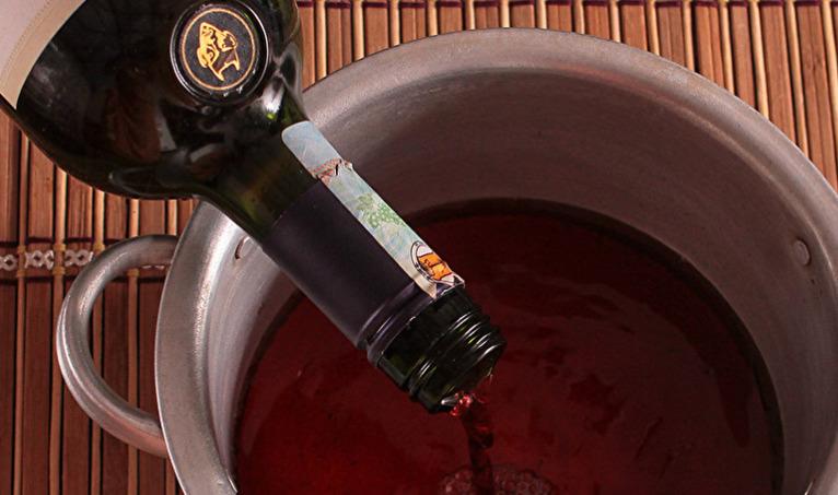 Вино поместить в кастрюлю и поставить на огонь